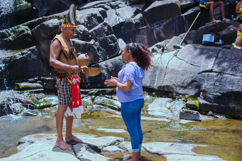 The Shaman standing with a lady in the river during the Naming Ceremony