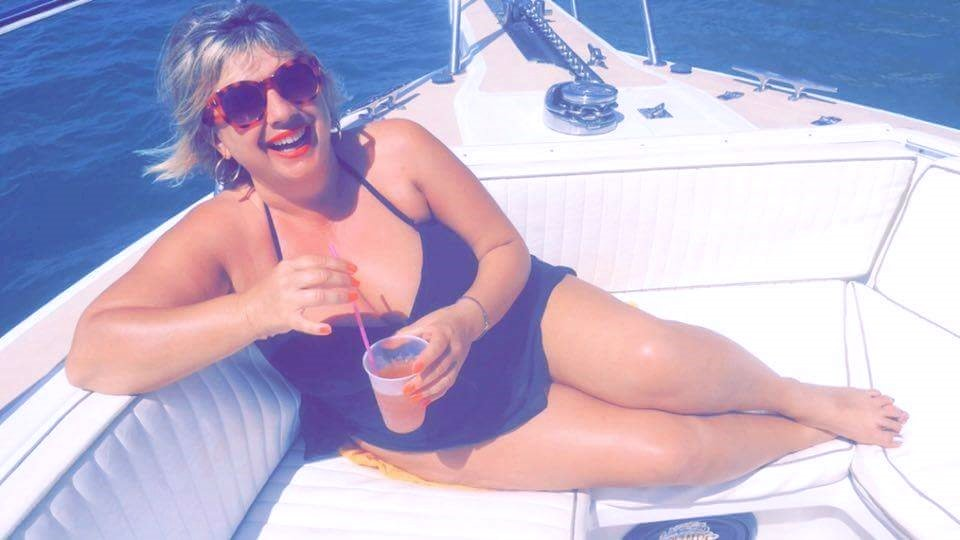 Trudy Nixon relaxing on a boat with a drink in hand