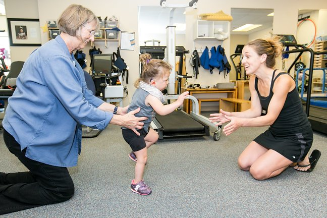 A little girl is walking between her two therapists as part of her therapy