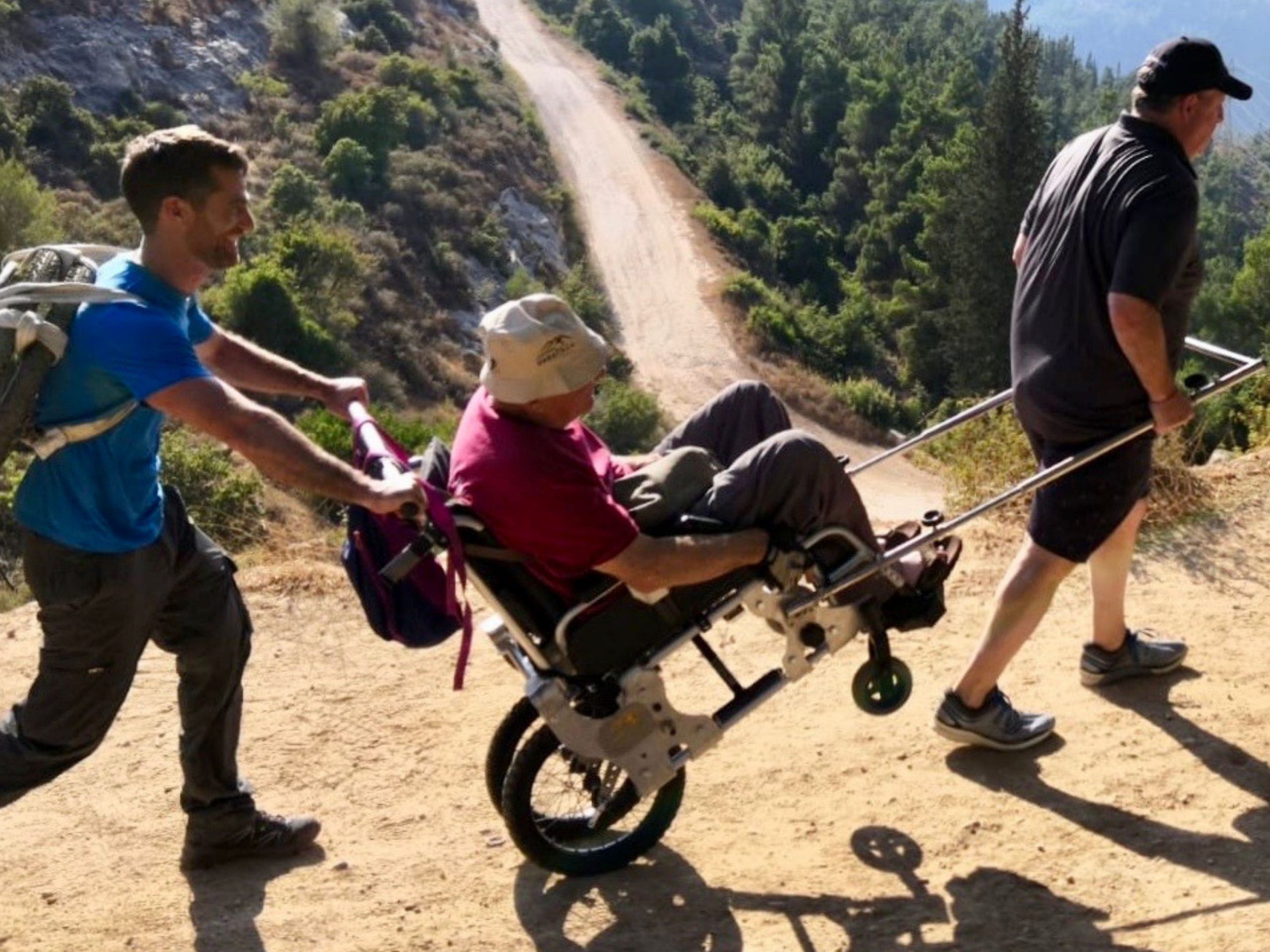 """hiking the hills of Jerusalem with paratrek. A man in an adapted wheelchair """"the Trekker"""" is geing cided alogn by one man at teh front pulling and one at the back, pushing"""