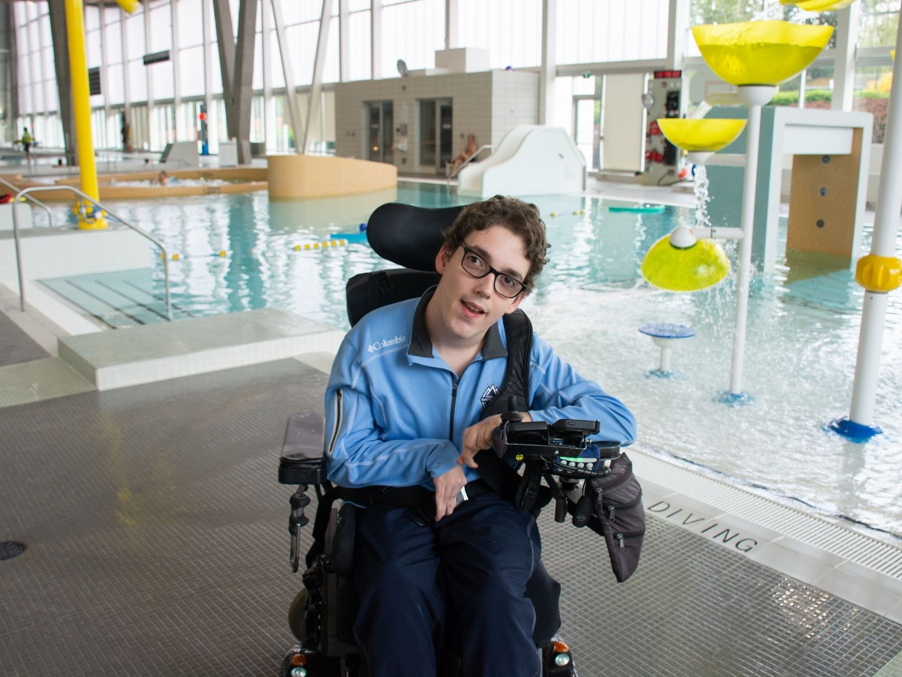 A man in a wheelchair at a swimming pool