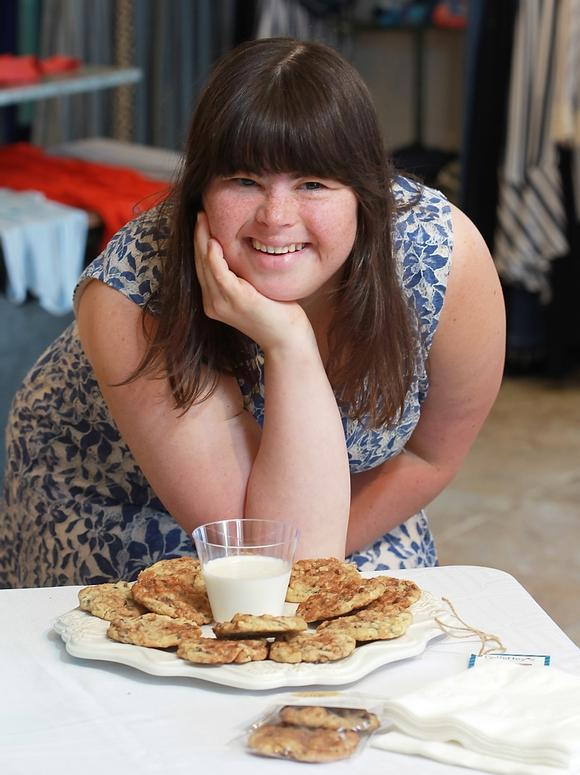 A smiling Collette Divitto of Collettey's Cookies with a plate of cookies and a glass of milk