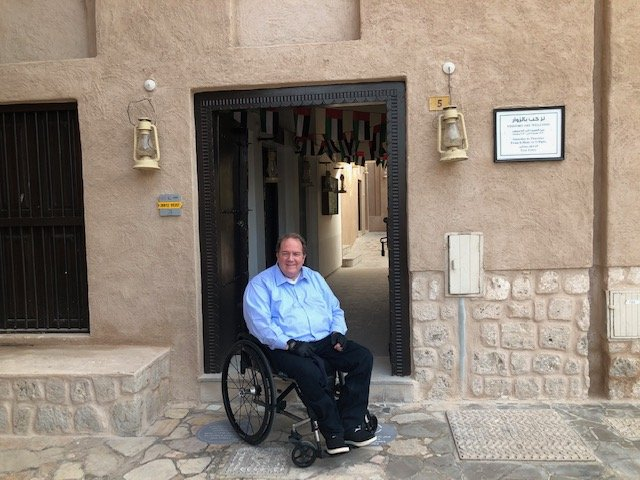 Fred in Dubai on his wheelchair wearing a blue shirt and black pants