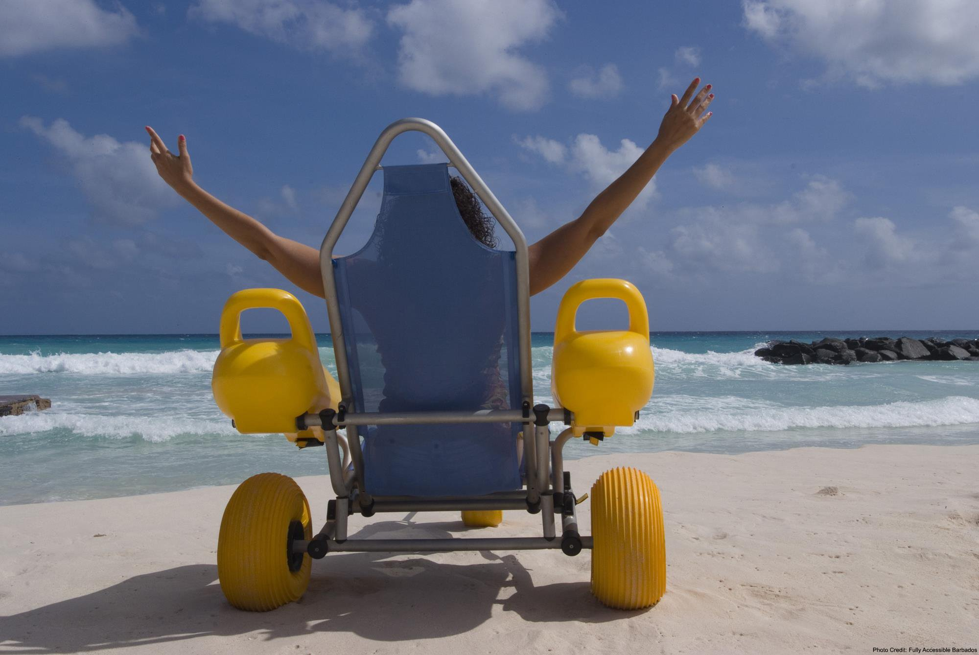 Lady in a beach wheelchair on the beach in Barbados with her hands out stretched