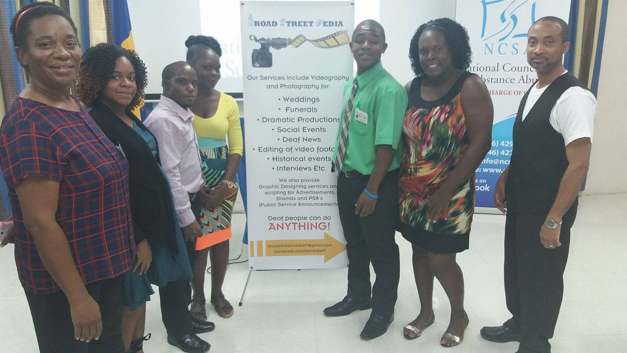 A group of 7 people representing the Broadstreet Media group, standing in front of a banner promoting their services