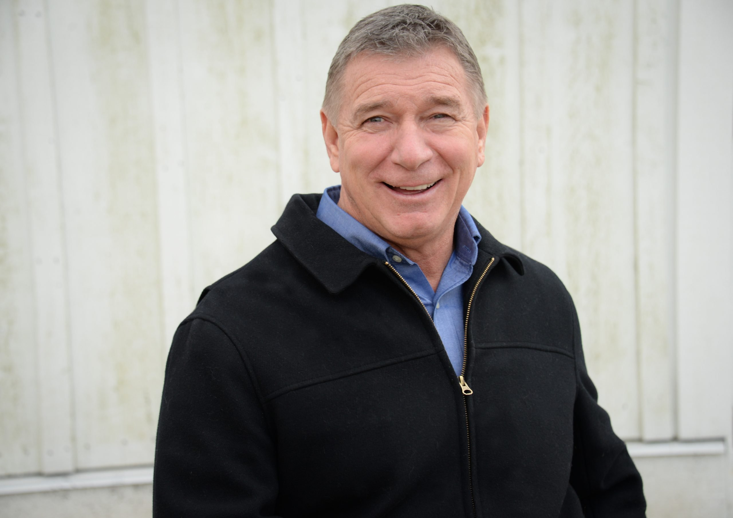 A smiling Rick Hansen wearing a blue shirt and black jacket
