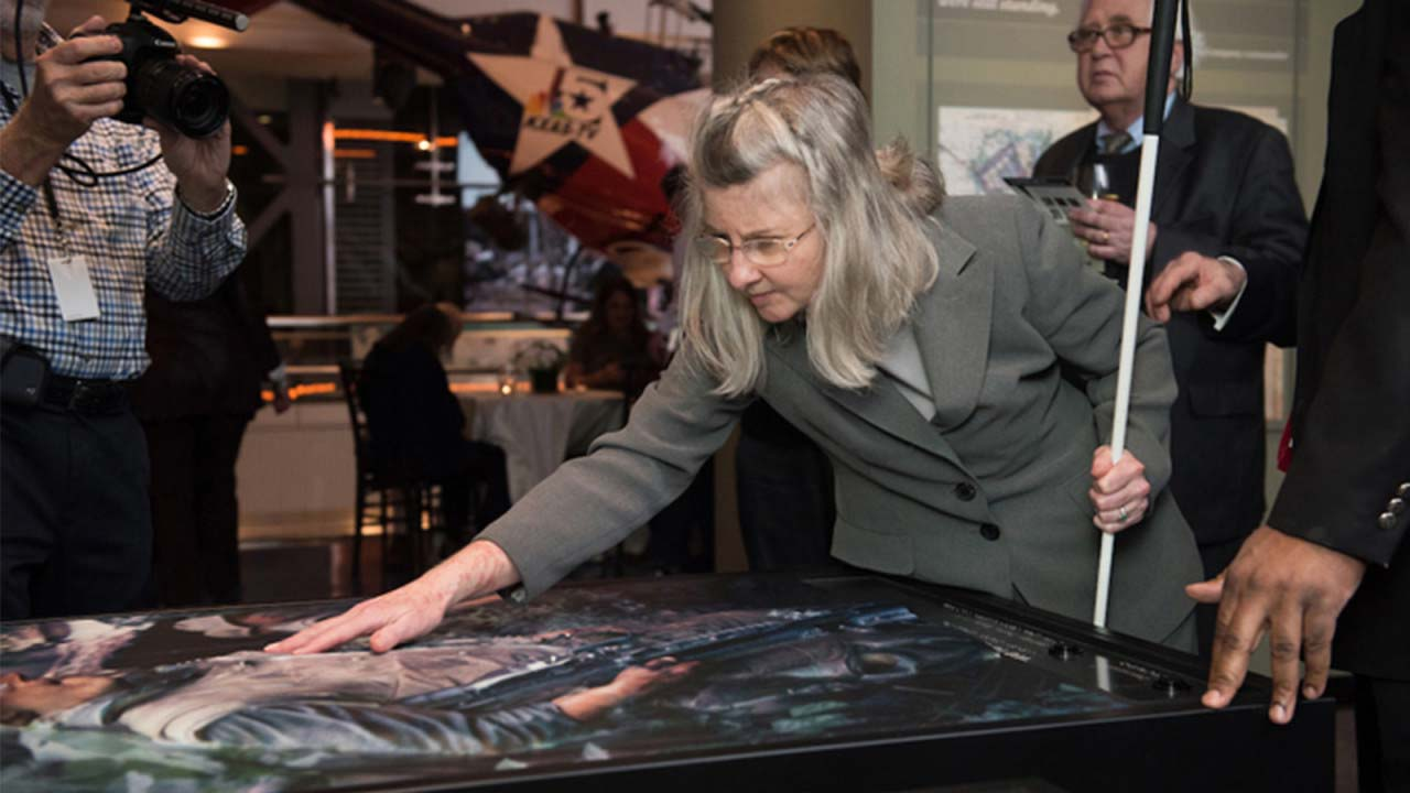 Lou Ann Blake, Deputy Executive Director for Blind Initiatives at the National Federation of the Blind, tries out a tactile photograph in the exhibition